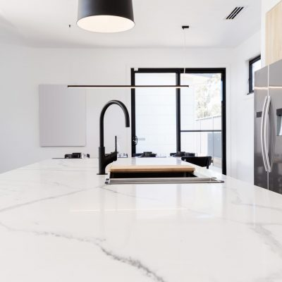 Carrera marble benchtop with black goose neck kitchen tap and black pendant